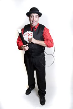 Christmas holiday Magician performs comical holiday theme magic show complete with juggling small xmas trees, sleight of hand close up magic, and holiday balloons sculptures
